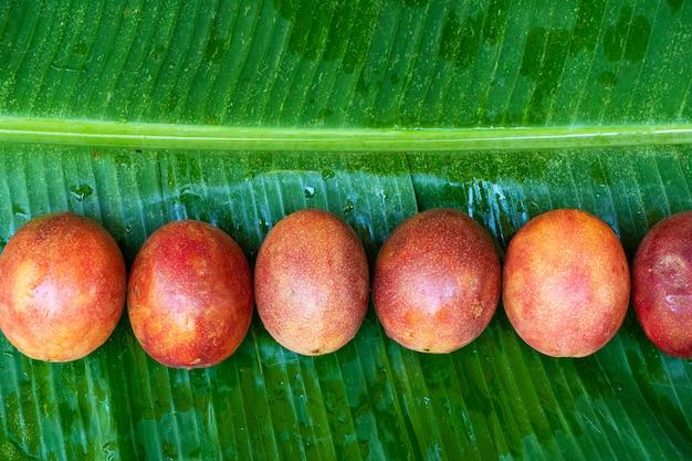 Rijpe passievrucht, op een nat bananenblad. vitaminen, fruit, gezond voedsel