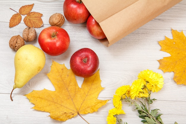 Rijpe peer, walnoten, rode appels met papieren zak, droge bladeren en gele bloemen op houten bureau. gezonde biologische voeding. herfst thema. bovenaanzicht.