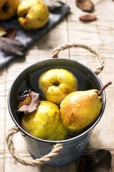 Rijpe peren en perenbladeren in een ijzeren emmer met water en op een houten tafel. rustieke stijl.