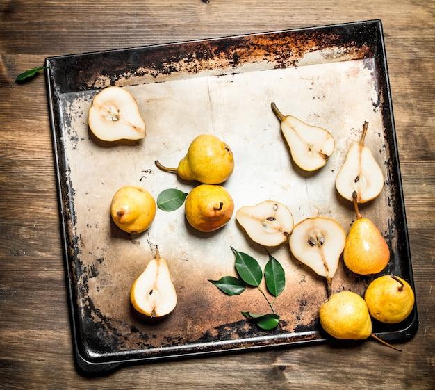Rijpe peren op bakplaat met groene bladeren op houten tafel.