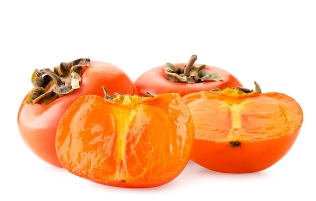 Rijpe persimmon en twee sappige helften close-up op een witte achtergrond. geïsoleerd