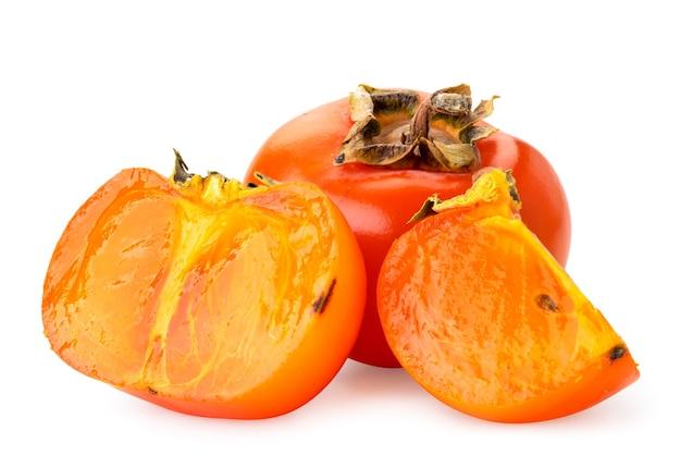 Rijpe persimmon, half en stuk close-up op een witte achtergrond. geïsoleerd