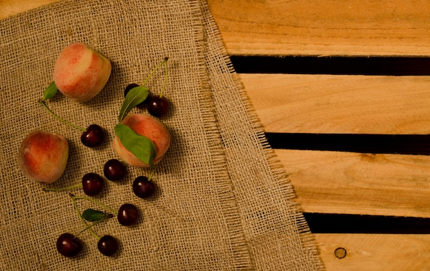 Rijpe perziken en kersen op zak en houten platen, plaats voor tekst, bovenaanzicht