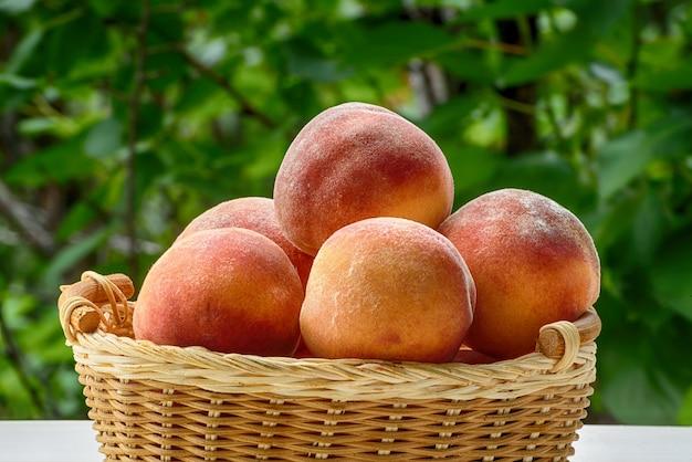 Rijpe perziken in een rieten mand