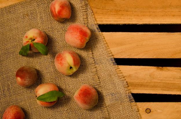 Rijpe perziken met bladeren op zak en houten platen