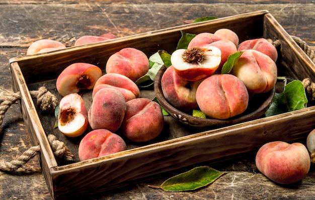 Rijpe perziken op een dienblad op een houten achtergrond