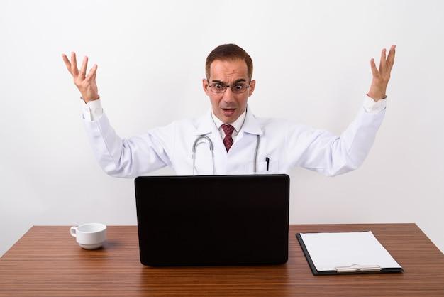 Rijpe perzische mensendokter die achter bureau werkt