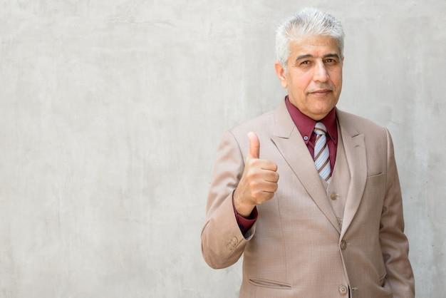 Rijpe perzische zakenman met grijs haar die duimen opgeeft tegen betonnen muur buitenshuis