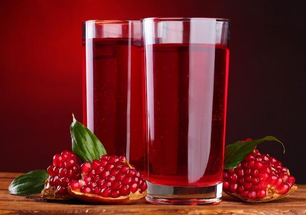 Rijpe pomergranate en glazen sap op houten tafel op rood
