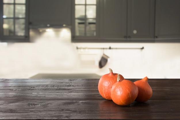 Rijpe pompoen op houten tafelblad in moderne keuken.