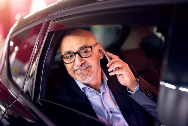 Rijpe professionele elegante succesvolle zakenman wordt gereden op de achterbank van de auto terwijl hij probeert te achterhalen wat de oorzaak is van zwaar verkeer.
