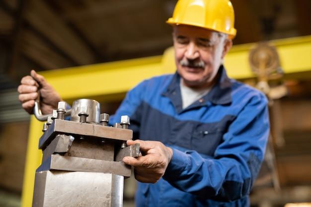 Rijpe professionele technicus van machineservice die generator of andere industriële apparatuur in werkplaats of hangar controleert