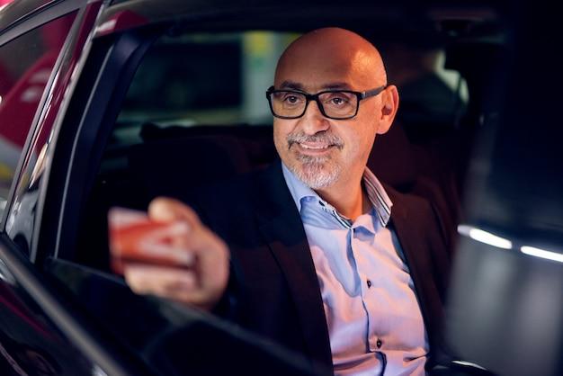 Rijpe professionele vrolijke succesvolle zakenman wordt gereden op de achterbank van de auto terwijl het uitdelen van zijn creditcard door het raam.