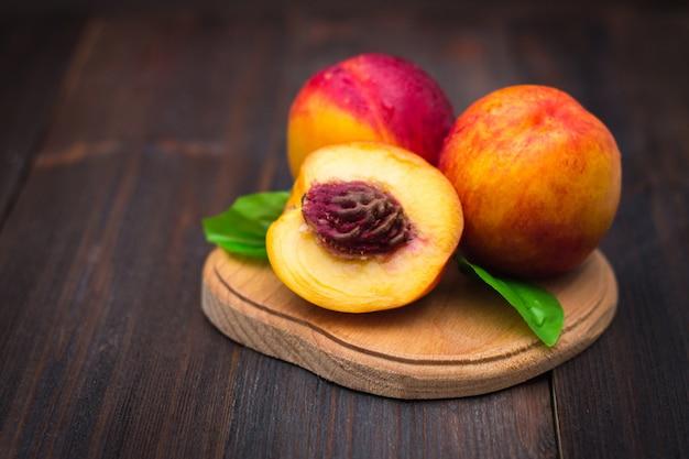 Rijpe pruimen en nectarines op een houten tafel. rijp fruit op een ruwe houten achtergrond.