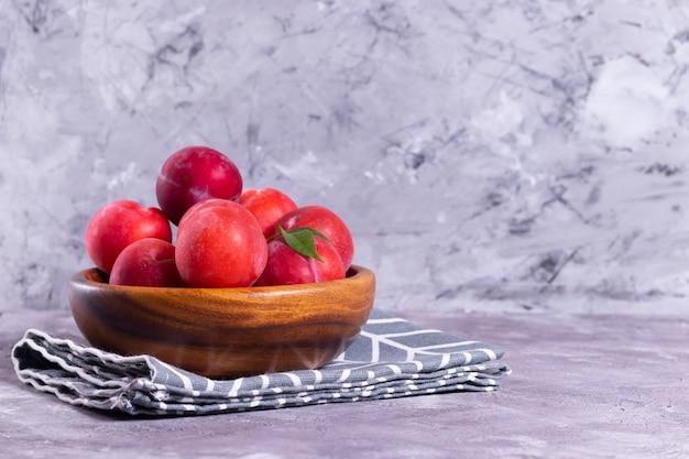 Rijpe pruimen in een houten plaat met een tissue servet