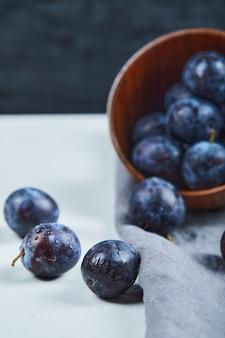 Rijpe pruimen in een kom met grijs tafelkleed op witte tafel.
