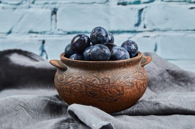 Rijpe pruimen in een kom op grijs tafelkleed