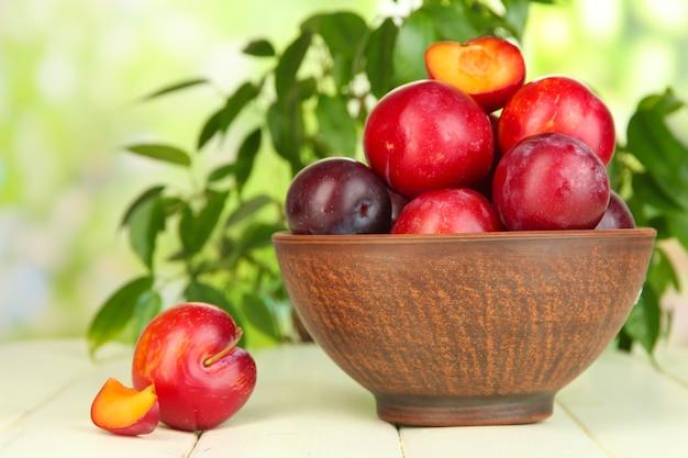 Rijpe pruimen in kom op houten tafel op natuurlijk