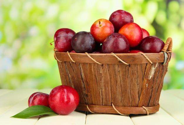 Rijpe pruimen in mand op houten tafel op natuurlijk