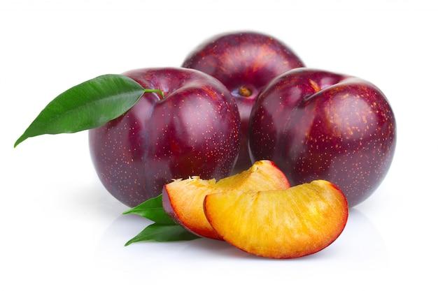 Rijpe purpere pruimvruchten met groene geïsoleerde bladeren