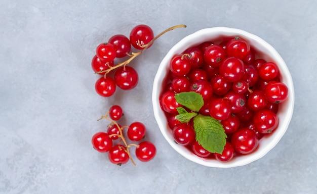 Rijpe rode aalbesbessen in witte komclose-up. verse aalbes met muntblaadjes op lichte dray stenen tafelblad weergave