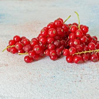 Rijpe rode aalbessen op een lichte achtergrond. verse zomerbessen, gezonde vitamines.