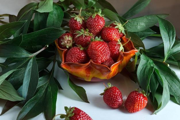 Rijpe rode aardbeien. bes in een oranje vaas