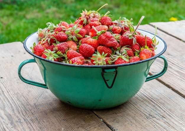 Rijpe rode aardbeien in kom op houten lijst