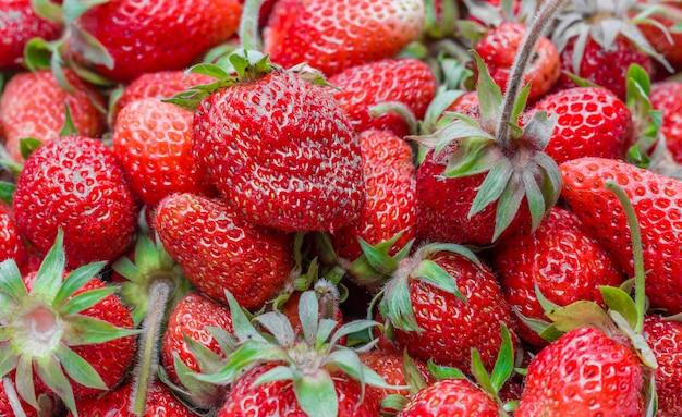 Rijpe rode aardbeien in kom op houten tafel bovenaanzicht