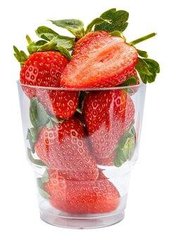 Rijpe rode aardbeien met groene bladeren en de helft van gesneden aardbei bovenop in het transparante plastic glas dat op een witte achtergrond wordt geïsoleerd