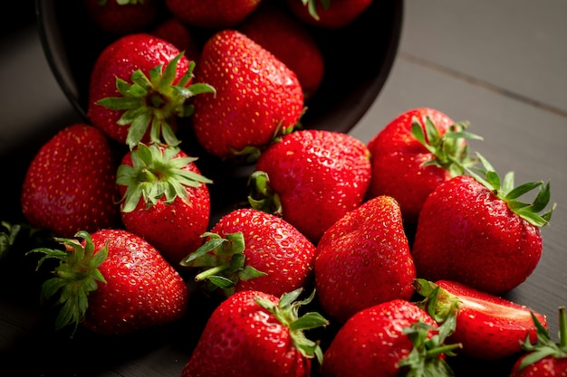 Rijpe rode aardbeien op zwarte houten tafel