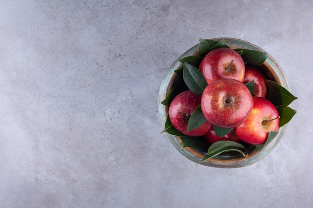 Rijpe rode appels met bladeren in een kom die op een steenachtergrond wordt geplaatst.