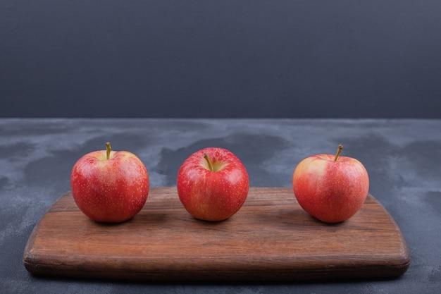 Rijpe rode appels op blauwe ondergrond.
