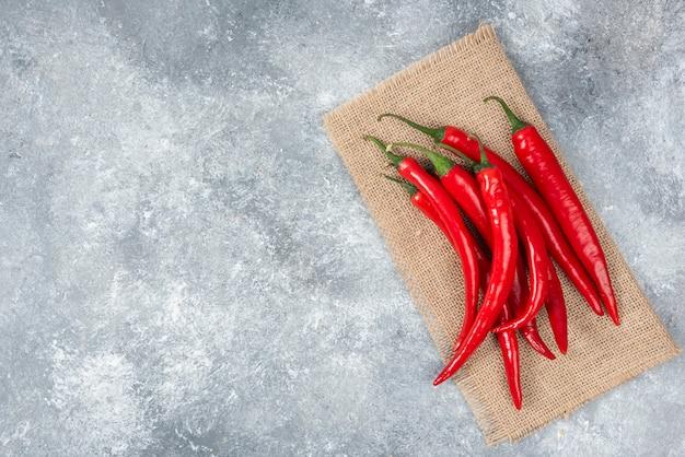 Rijpe rode chilipepers met een zak op marmeren oppervlak.