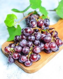 Rijpe rode druif met bladeren op wit.