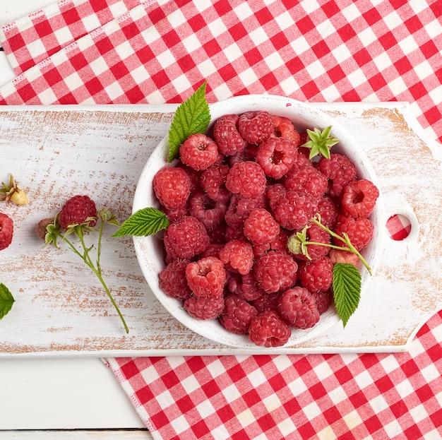 Rijpe rode frambozen in een witte houten plaat op een tafel van planken