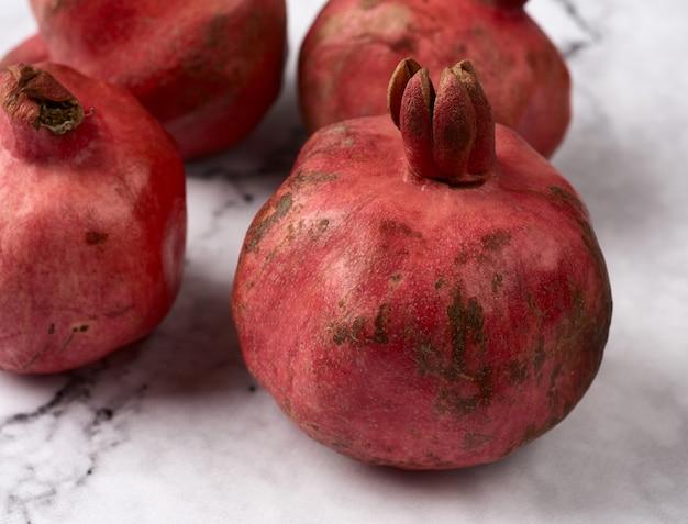 Rijpe rode granaatappels op een witte marmeren tafel