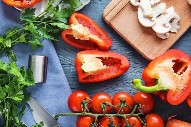 Rijpe rode paprika's met andere groenten op tafel