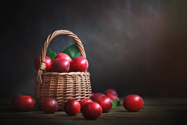 Rijpe rode pruimen in een rieten mand op een houten tafel.