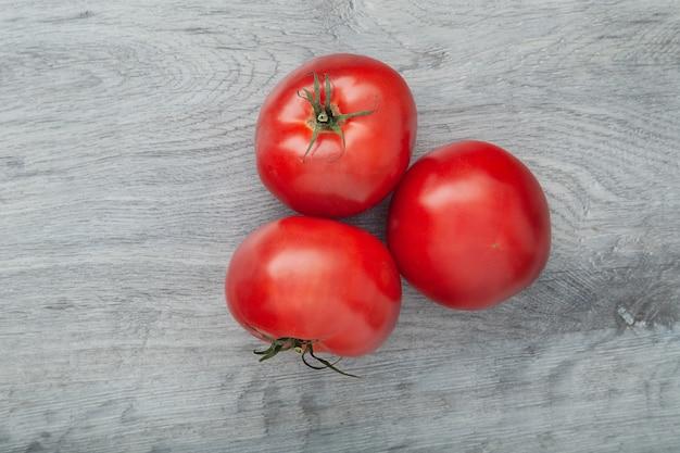 Rijpe rode tomaten die op de grijze qoodentafel worden geplaatst