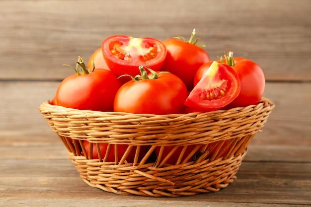 Rijpe rode tomaten in mand op grijs