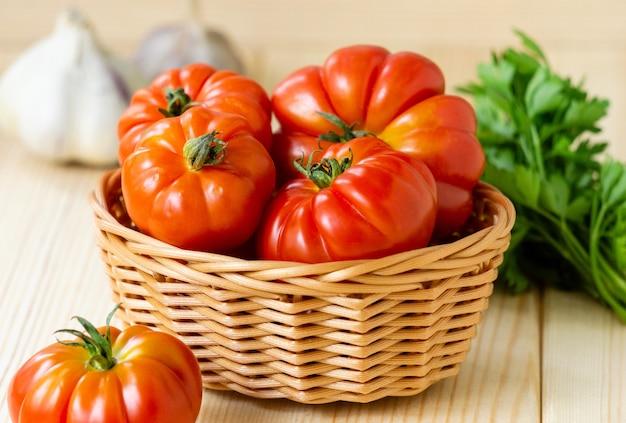 Rijpe rode tomaten in mand op lichte houten achtergrond.