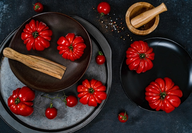 Rijpe rode tomaten liggen op een zwarte plaat op een zwarte achtergrond met houten schotels, bovenaanzicht.