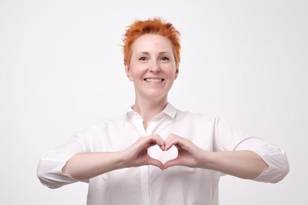 Rijpe roodharige vrouw in een wit overhemd