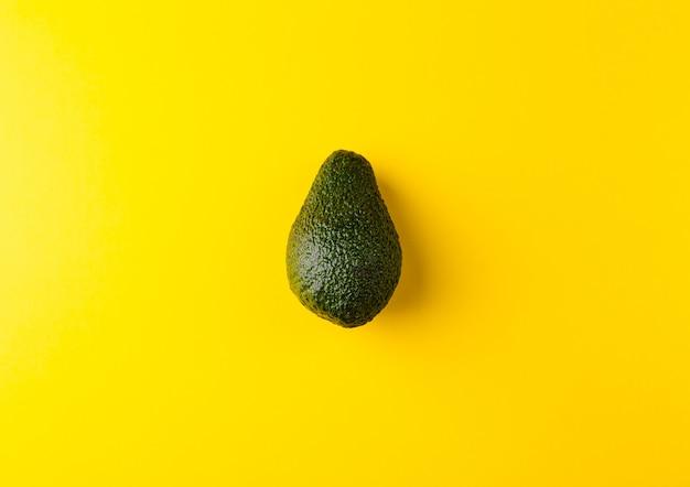 Rijpe sappige avocado die op een gele stevige achtergrond wordt geïsoleerd.