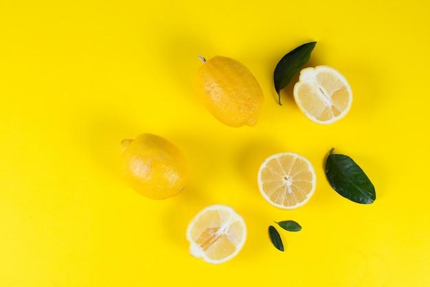 Rijpe sappige citroenen met bladeren op een gekleurde gele achtergrond