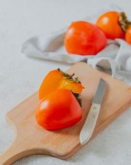 Rijpe sappige oranje persimmon op een houten bord en een witte tafel.