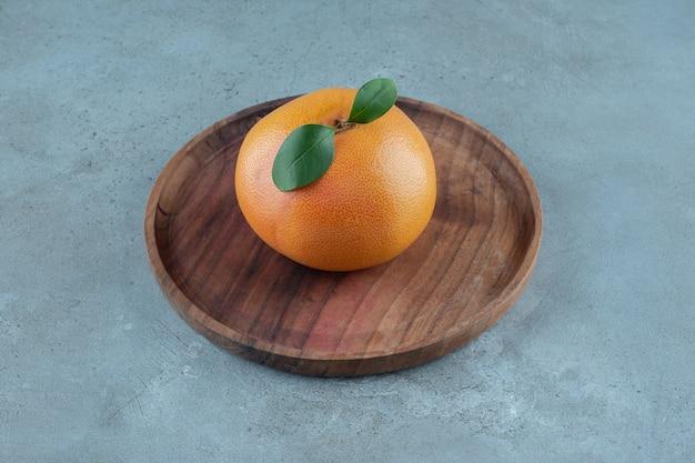 Rijpe sappige sinaasappel op een houten plaat, op de marmeren achtergrond. hoge kwaliteit foto