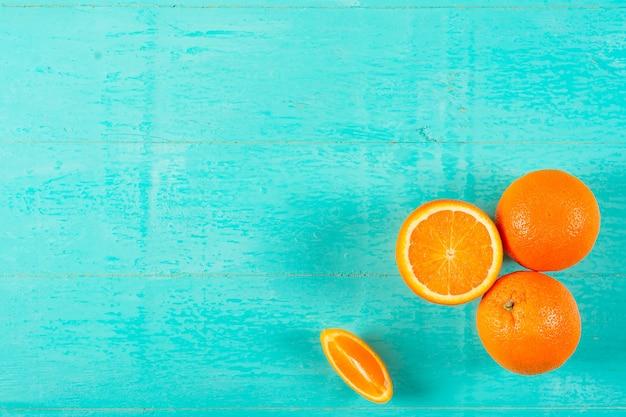 Rijpe sappige sinaasappelen op een blauwe houten achtergrond