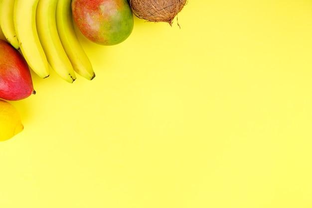 Rijpe sappige tropische zomer seizoensfruit mango kokosnoot kiwi bananen aardbeien op gele achtergrond.
